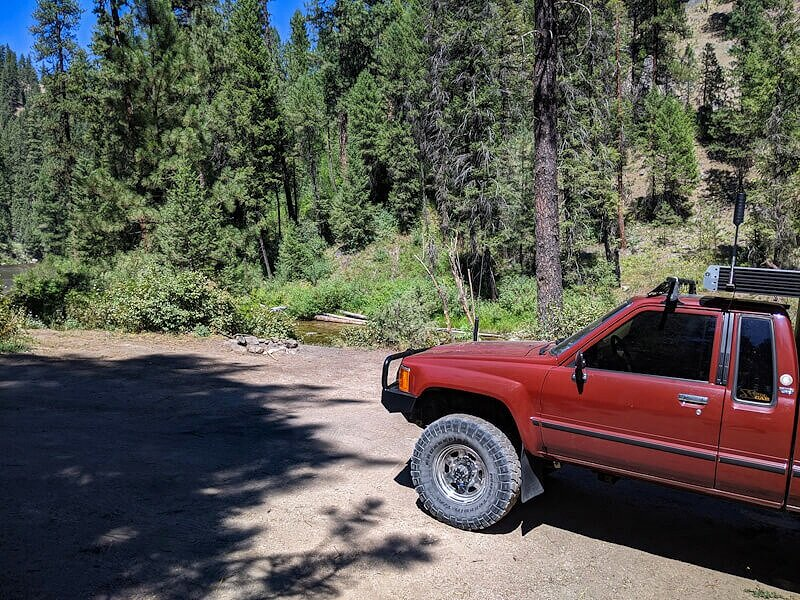 Toyota truck shell camper at free campsite in Idaho national forest by a hot spring.